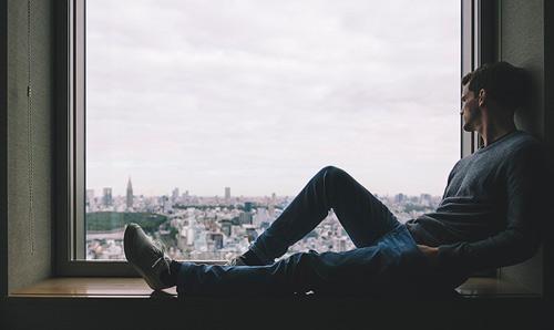 man zit onderuit en kijkt dromerig uit het raam vanuit een vensterbank